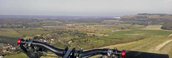 View of Fulking from escarpment with MTB handlebars in foreground